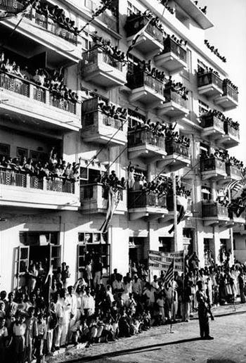 People waving Pakistani and American flags from the balconies of their apartments at Karachi Burns Road as US President Dwight Eisenhower's motorcade passes by during his visit to Pakistan in 1959.