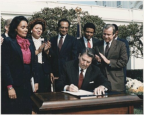 President Ronald Reagan signs legislation to create a federal holiday honoring Martin Luther King, Jr. in the Rose Garden of the White House on November 2, 1983.