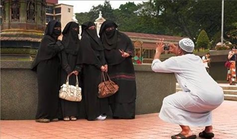 man taking pic of hijabbed women
